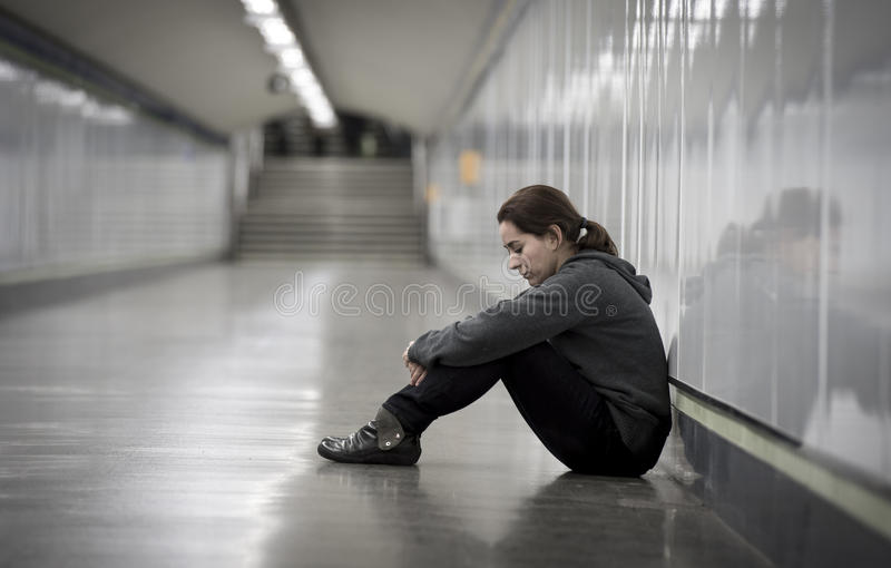 Young sad woman in pain alone and depressed at urban subway tunnel ground worried suffering depression. Young sad woman in pain sitting alone and depressed at stock photo