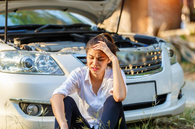 Young sad woman shouts holding his head sitting outside the car and she waits for assistance near her car broken down on the road royalty free stock images