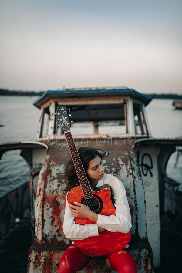 A young woman sits with guitar on old abandoned ship royalty free stock image