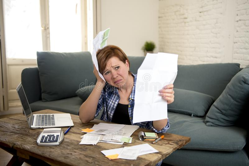 Young sad worried and desperate woman banking and accounting home monthly and credit card expenses with computer laptop royalty free stock photography