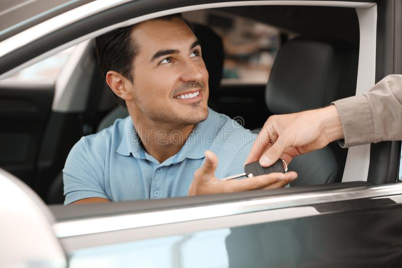 Young salesman giving car key to customer in  auto dealership, closeup stock photo