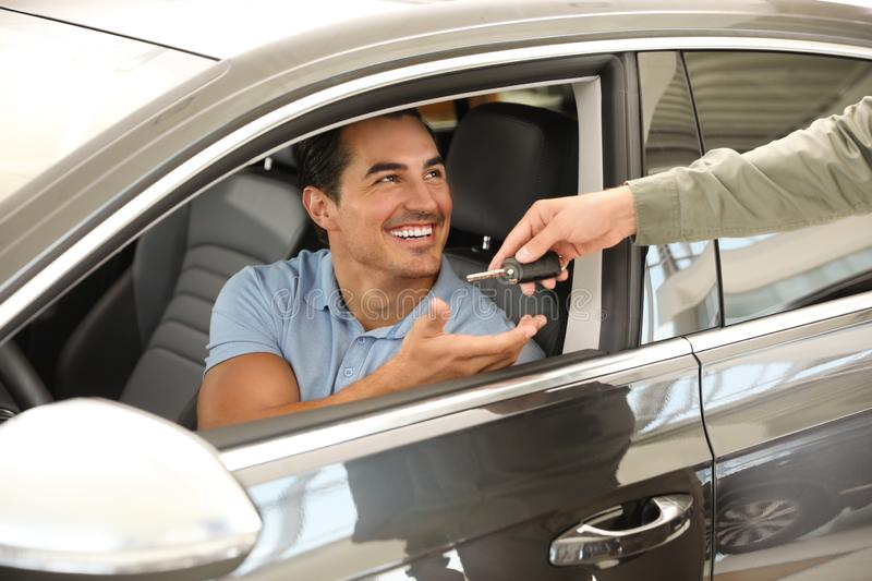 Young salesman giving car key to customer in  auto dealership, closeup. Young salesman giving car key to customer in modern auto dealership, closeup royalty free stock image