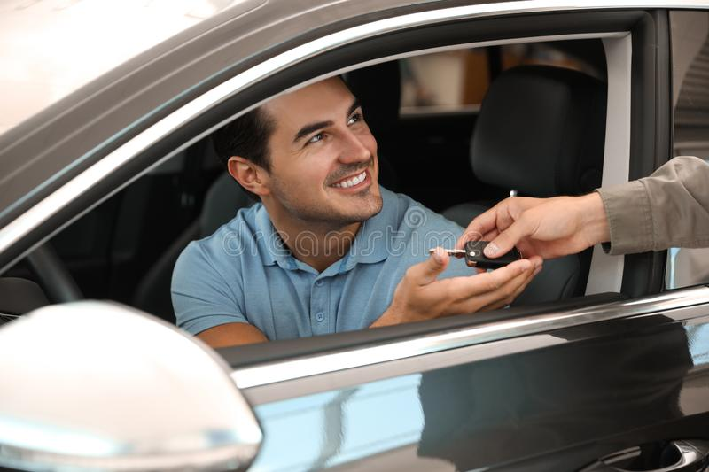 Young  giving car key to customer in modern auto dealership, closeup. Young salesman giving car key to customer in modern auto dealership, closeup stock image