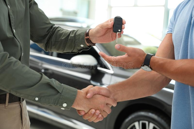 Young salesman shaking hands with  and giving car key in modern auto dealership, closeup. Young salesman shaking hands with customer and giving car key in modern royalty free stock photos