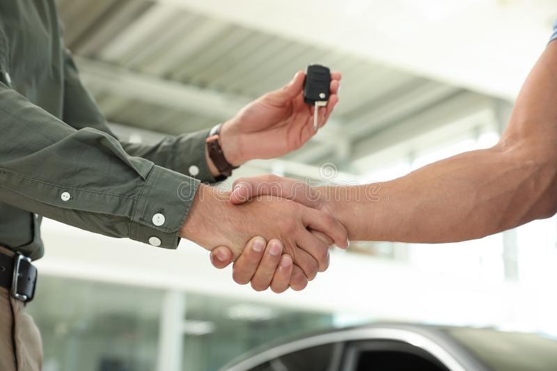 Young salesman shaking hands  customer and giving car key in modern auto dealership, closeup. Young salesman shaking hands with customer and giving car key in stock photography