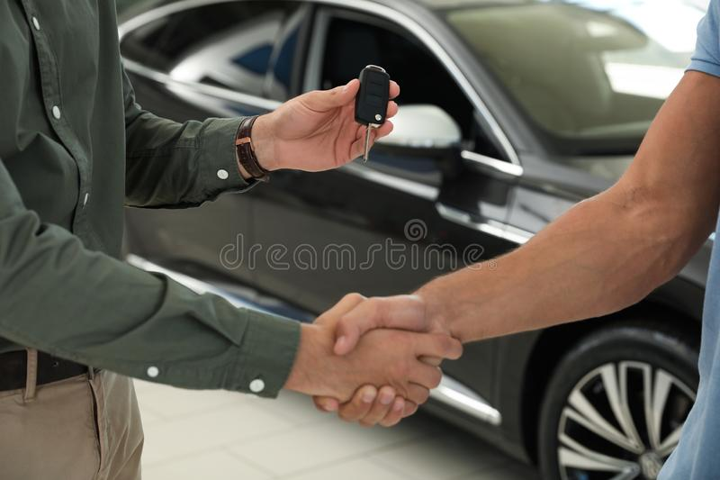 Young salesman shaking hands with  and giving car key in modern auto dealership, closeup. Young salesman shaking hands with customer and giving car key in modern royalty free stock photo