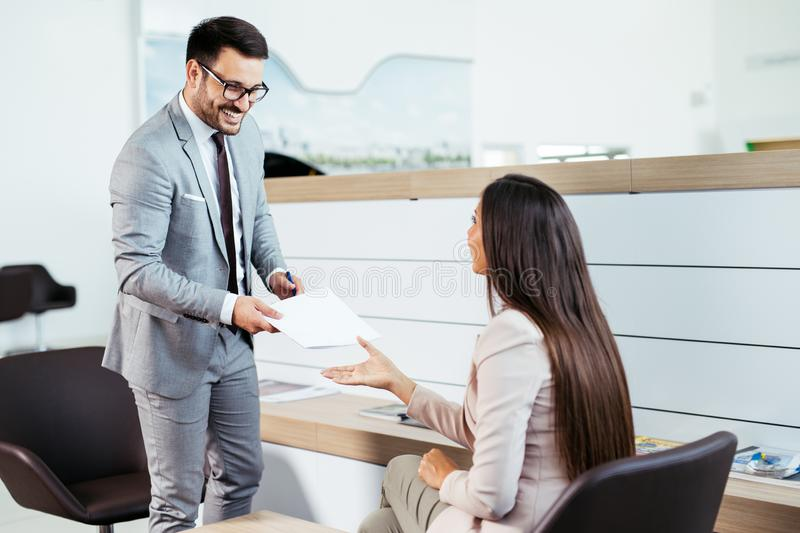 Salesperson selling cars at dealership to buyer royalty free stock image