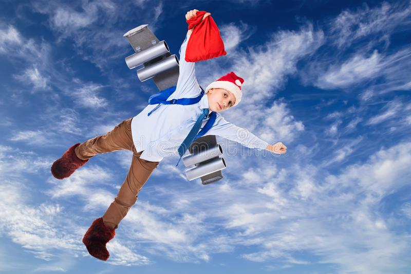 Young Santa Claus flying in the sky with presents for Christmas. On a jet pack royalty free stock images