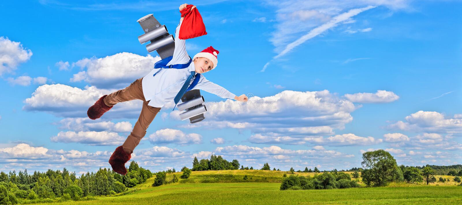 Young Santa Claus flying in the sky with presents for Christmas. On a jet pack stock photography