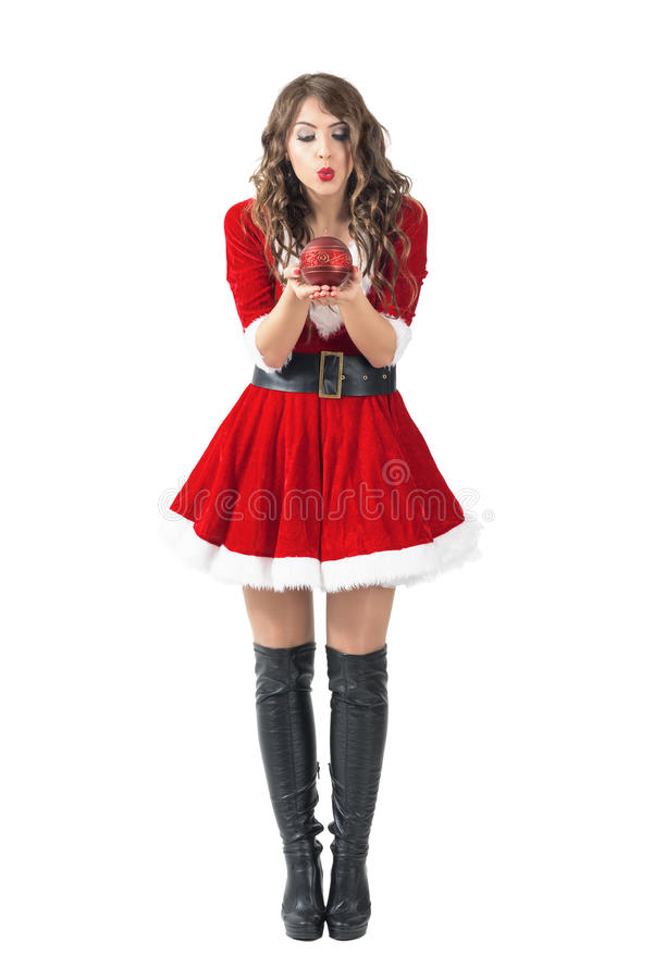 Young Santa girl blowing round decorative candle royalty free stock images