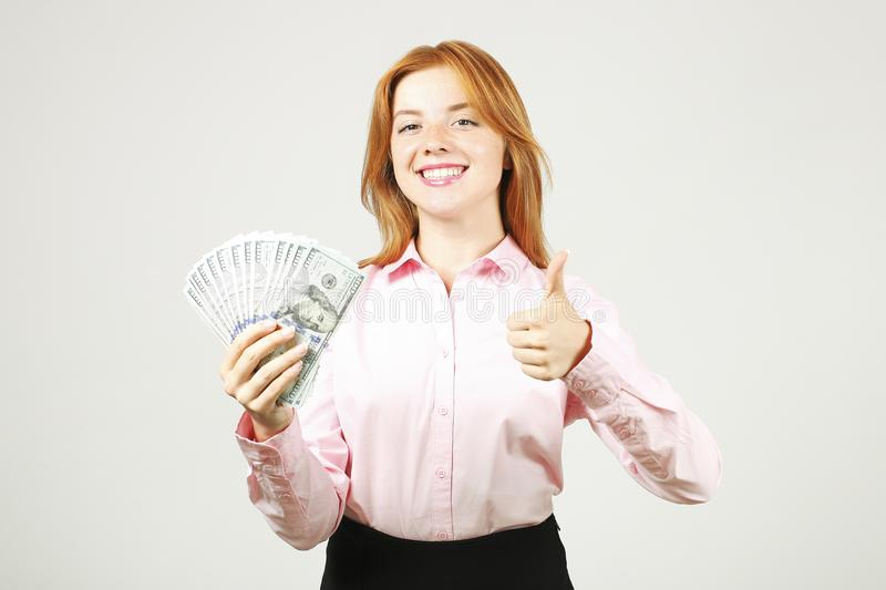 Attractive young businesswoman posing with bunch of USD cash in hands showing positive emotions and happy facial expression. royalty free stock photo