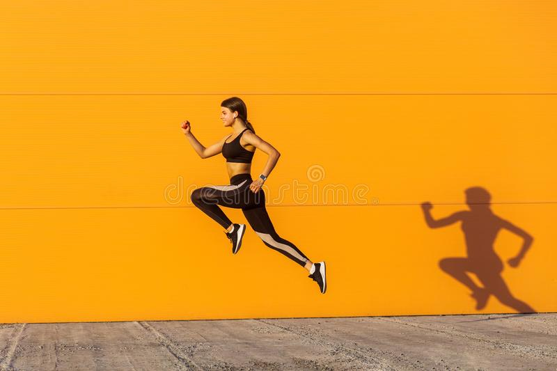 Young satisfied sporty beautiful woman with fit body jumping and running, hurry up against orange wall background. Gymnast jumping royalty free stock image