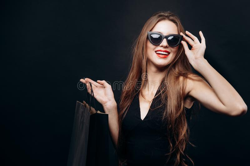 Young Satisfied Trendy Customer Adjusting Sunglasses and Looking Ahead royalty free stock photography