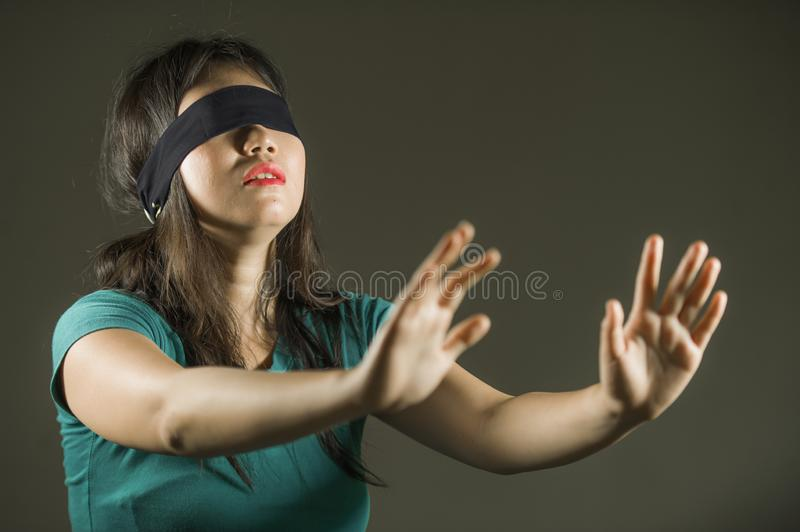Young scared and blindfolded Asian Chinese teenager girl lost and confused playing dangerous internet viral challenge on. Dark background under edgy and stock photo