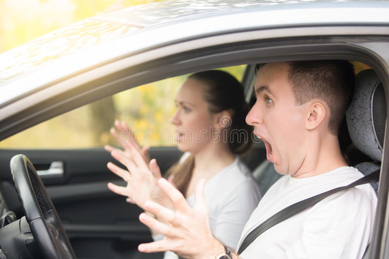 Young scared man driver and a woman passenger stock image