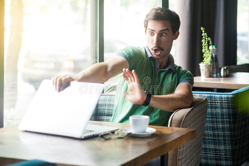 Young scared or shocked businessman in green t-shirt sitting and closing laptop because something crazy inside he seen and afraid stock photos