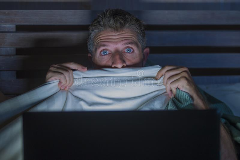 Young scared and stressed man in bed watching internet horror movie late night with laptop computer or bedroom television in. Lifestyle portrait of young scared royalty free stock image