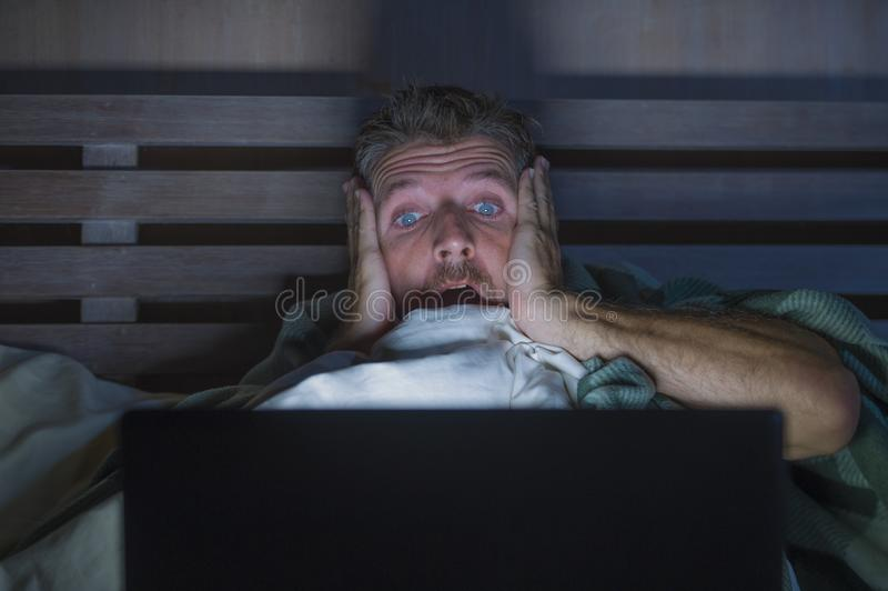 Young scared and stressed man in bed watching internet horror movie late night with laptop computer or bedroom television in. Lifestyle portrait of young scared royalty free stock photography