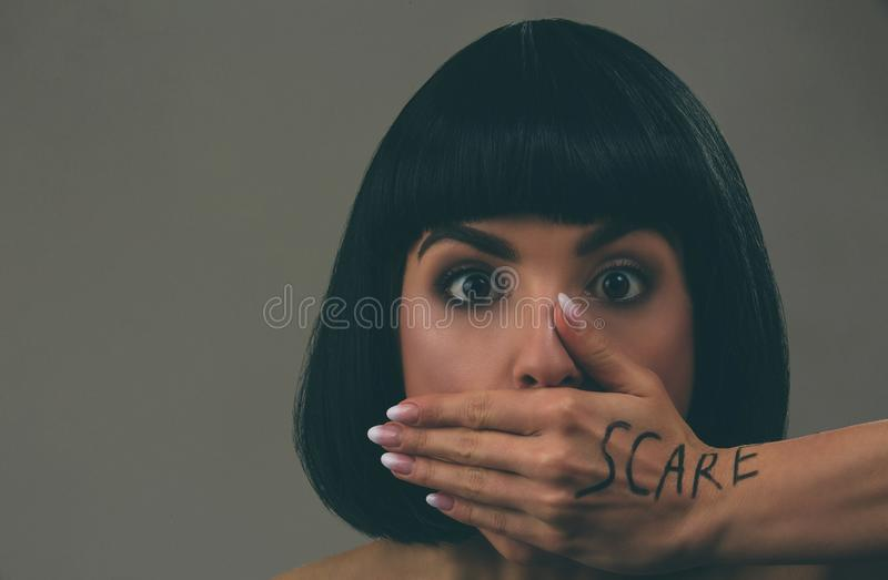 Young scared woman with black hair posing on camera. Scared afraid model look straight. Mouth closed with hand. Fear in. Eyes. Bob haircut. Isolated on dark stock image