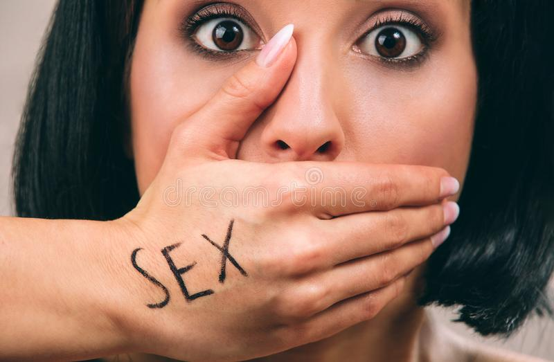 Young scared woman with black hair posing on camera. Hand on mouth. Written work sex. Concept harassment. Cutview. Isolated on light background stock photos