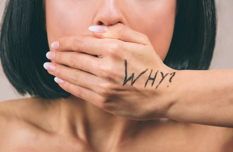 Young scared woman with black hair posing on camera. Mouth closed with hand. Written work why. Sexual harassment. Concept of obsession. Cut view. Isolated on stock photo