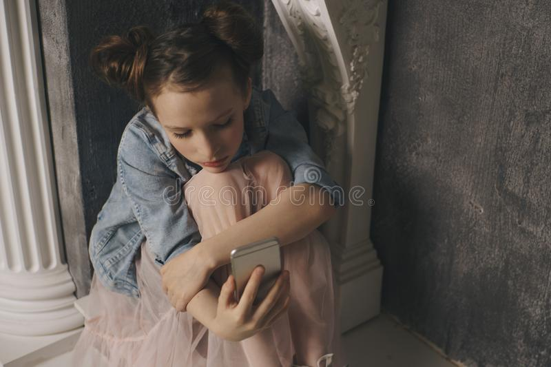 Young scared and worried teenager girl holding mobile phone as internet stalked victim abused and cyberbullying or cyber royalty free stock photos