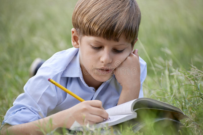 Young school boy doing homework alone, lying on grass stock photography