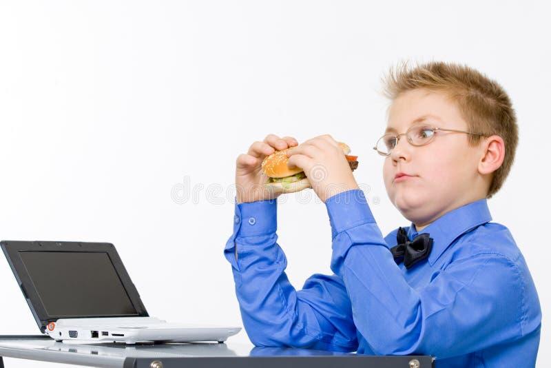 Young school boy eating hamburger royalty free stock images