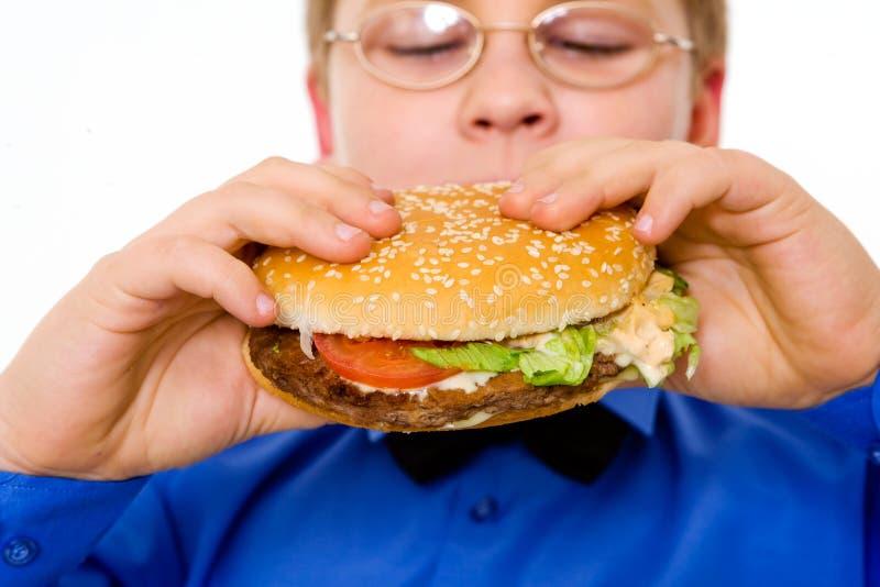 Young school boy eating hamburger royalty free stock photos
