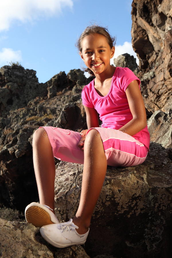 Young school girl sitting in sunshine on rocks. Full body shot of young mixed race school girl with a cute smile sitting on rocks outdoors in the late afternoon royalty free stock photo