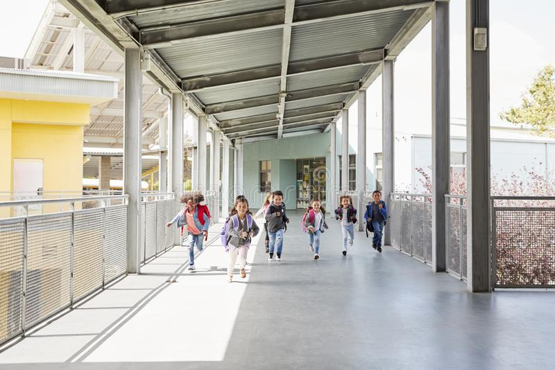 Young school kids running on a walkway in their school royalty free stock photography