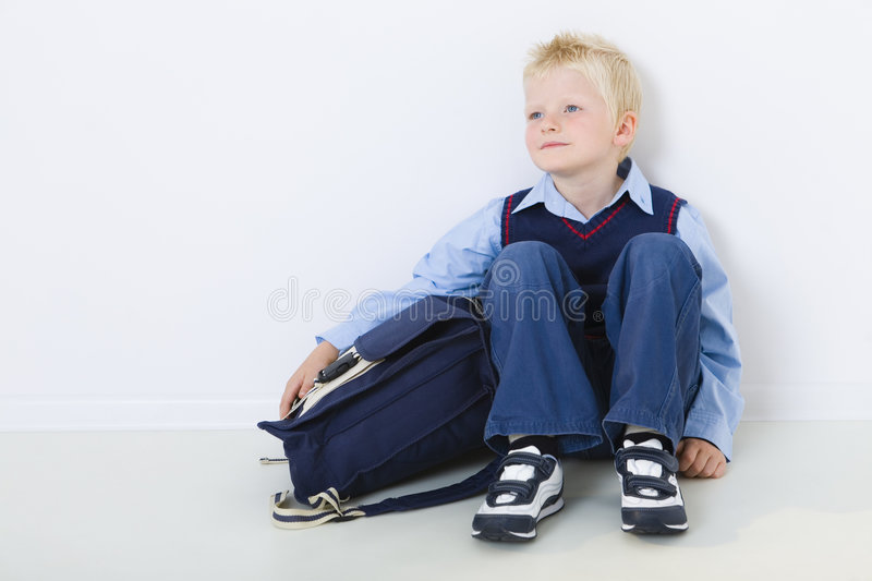 Young schoolboy. Smiling young schoolboy sitting on the floor with schoolbag. Front view royalty free stock images