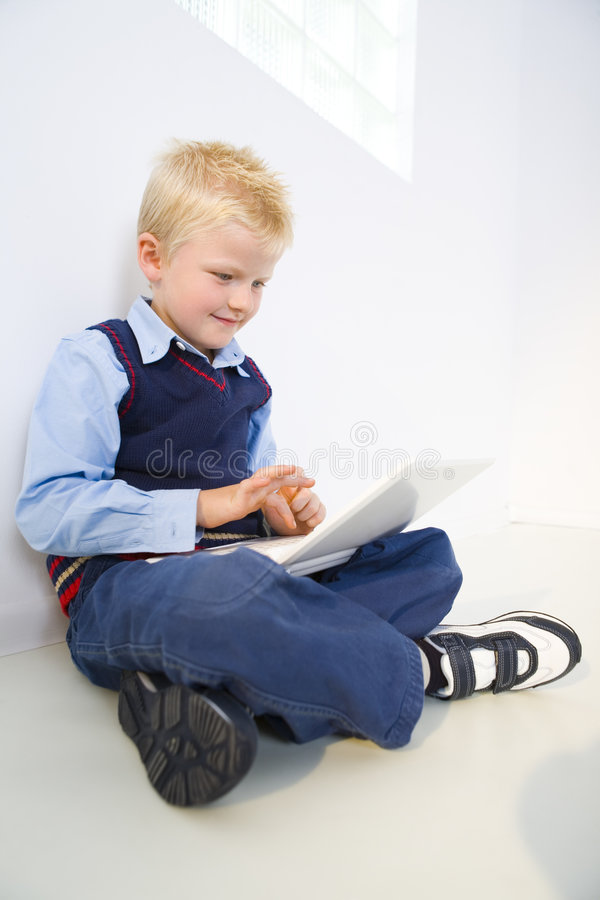 Young schoolboy with laptop royalty free stock image