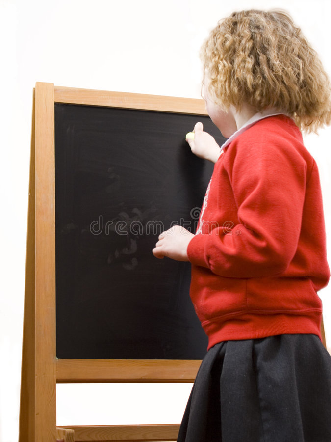 Young schoolgirl on blackboard. royalty free stock image