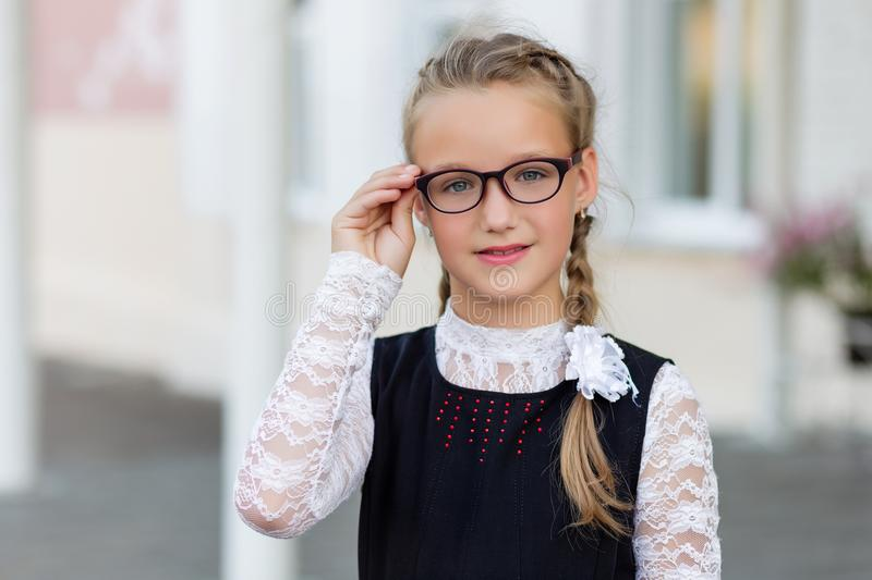 Young schoolgirl with glasses and school uniform outdoors in fro stock photos