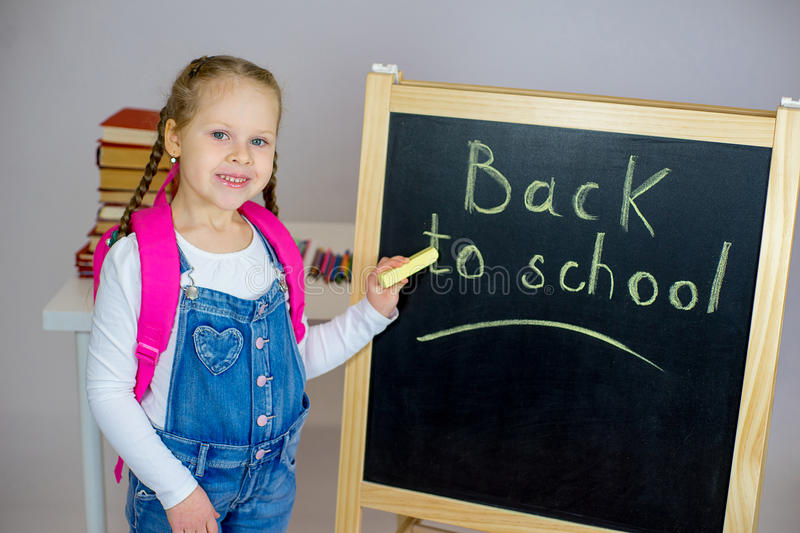 Young schoolgirl near the blackboard royalty free stock images