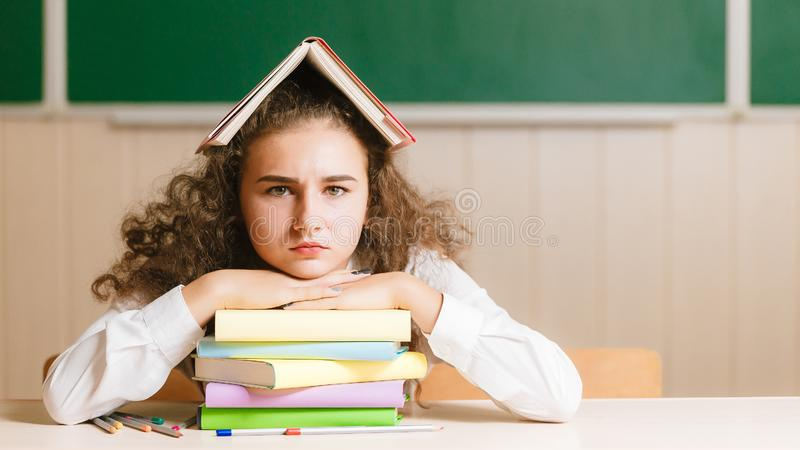 Young schoolgirl sitting at her desk on the background of the blackboard and holding a book on her head royalty free stock photography