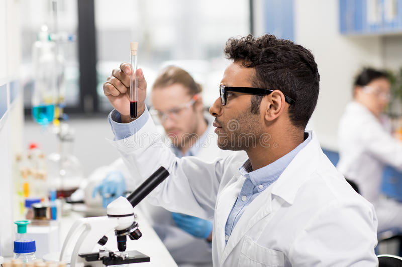 Young scientist in eyeglasses looking at test tube in research laboratory stock photos