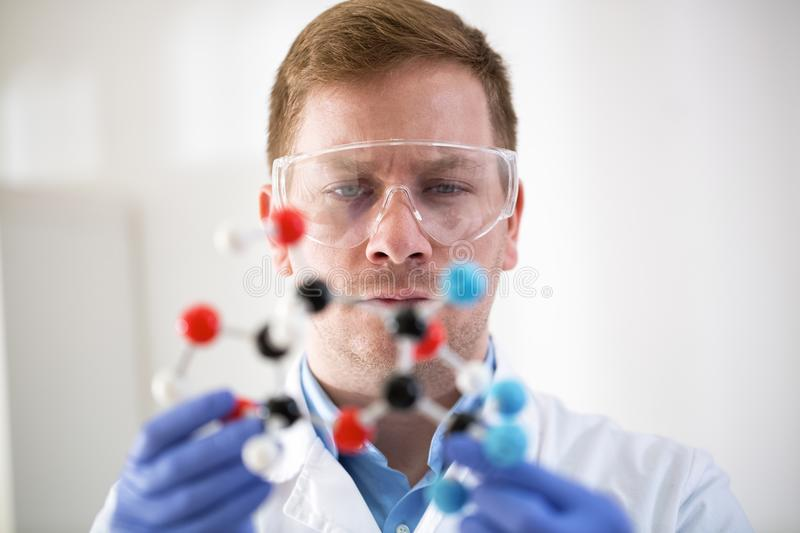 Young scientist holding molecular model at private clinic. Young scientist holding molecular model at private pro clinic stock photo