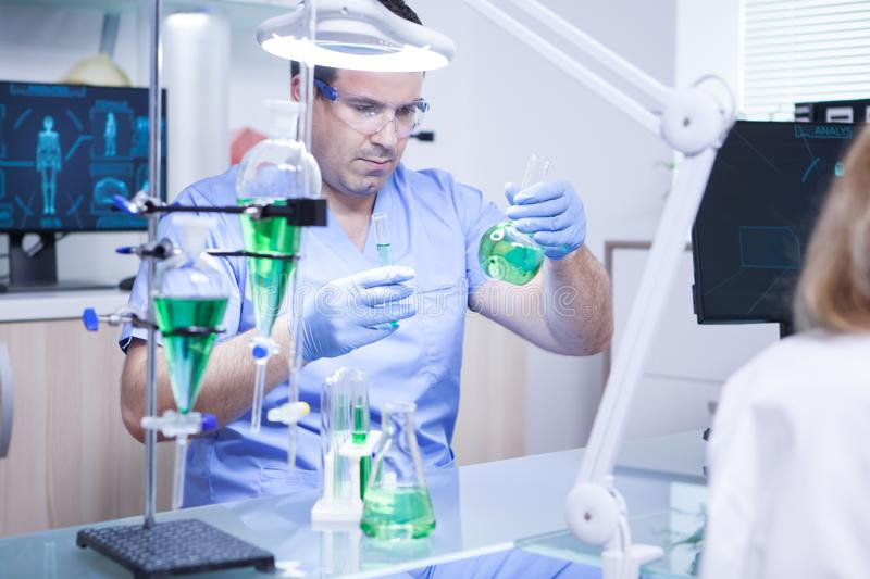 Young scientist holding two test tubes in a research laboratory royalty free stock photography