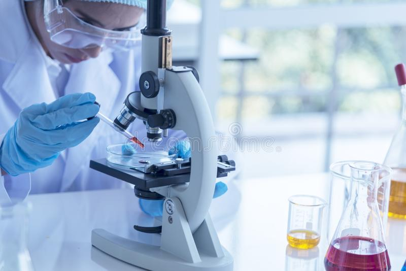 Young scientist looking through a microscope in a laboratory. Young scientist doing some research.Portrait woman of confident scie stock photos