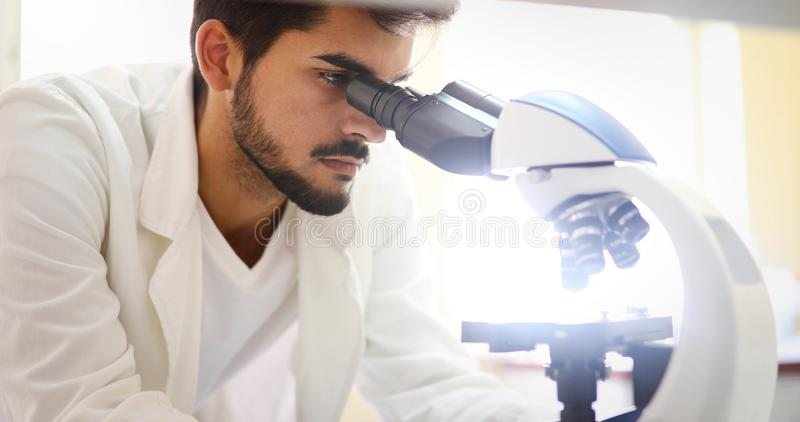 Young scientist looking through microscope in laboratory. Young male scientist looking through microscope in laboratory royalty free stock photos