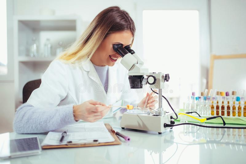 Young scientist looking through a microscope in a laboratory. stock photo