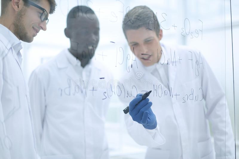 Young scientist makes notes on a glass Board. Concept of education royalty free stock photo