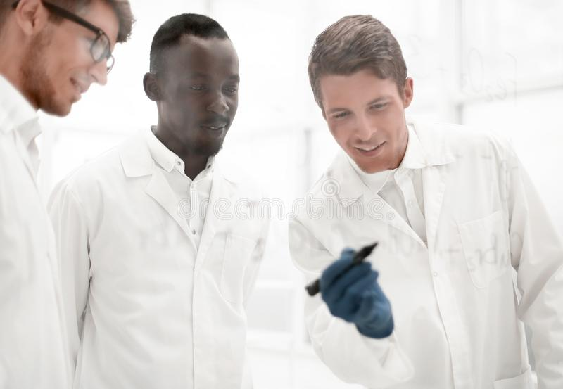 Young scientist makes notes on a glass Board. Concept of education stock image
