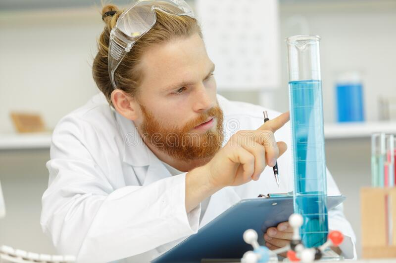 Young scientist observing liquid reagent in laboratory royalty free stock photos
