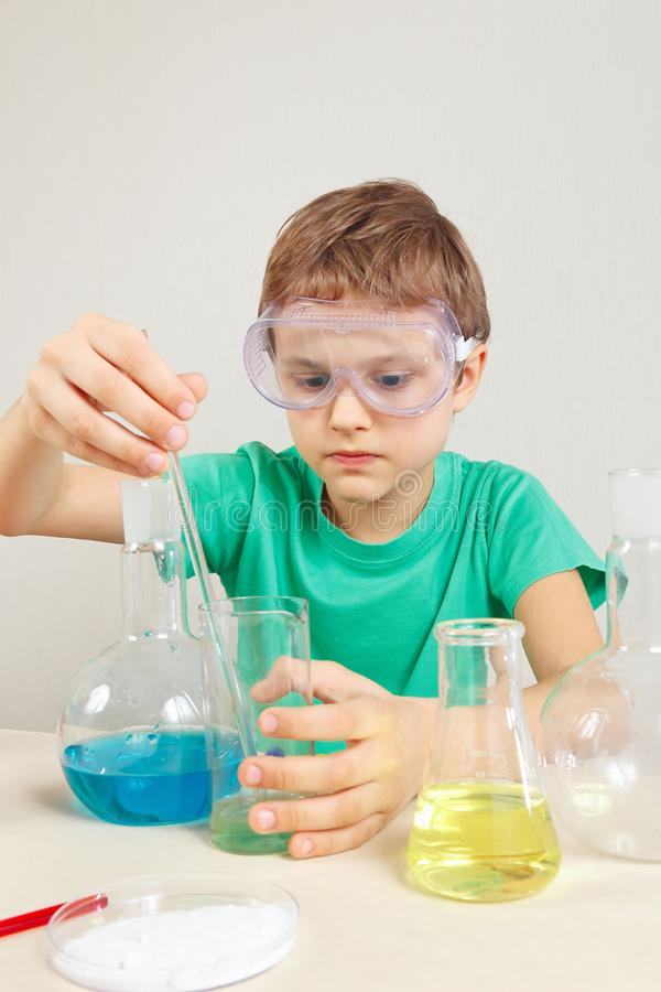 Young scientist in safety goggles doing chemical experiments in laboratory. Young scientist in safety goggles doing chemical experiments in the laboratory stock photos