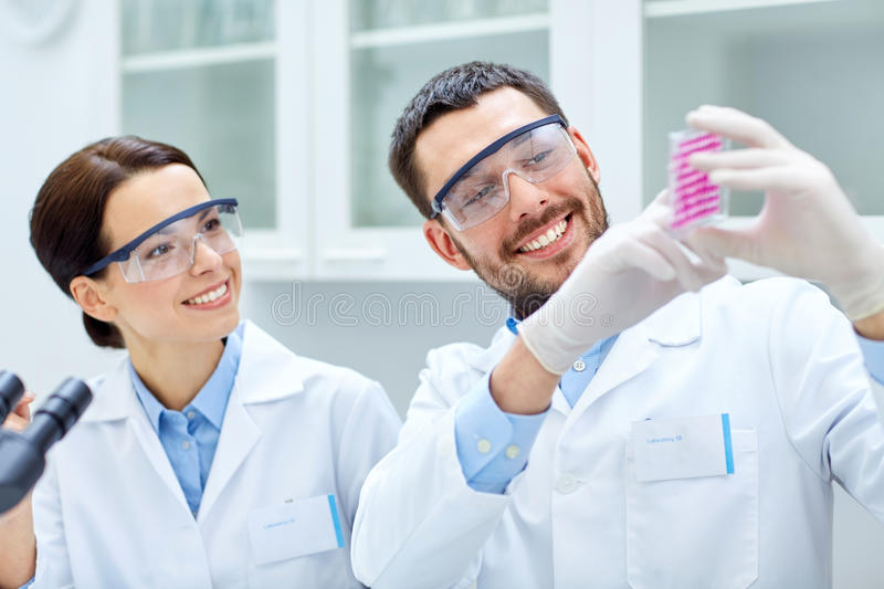 Young scientists making test or research in lab. Science, chemistry, biology, pharmacy and people concept - young scientists with pipette and flask making test stock photos