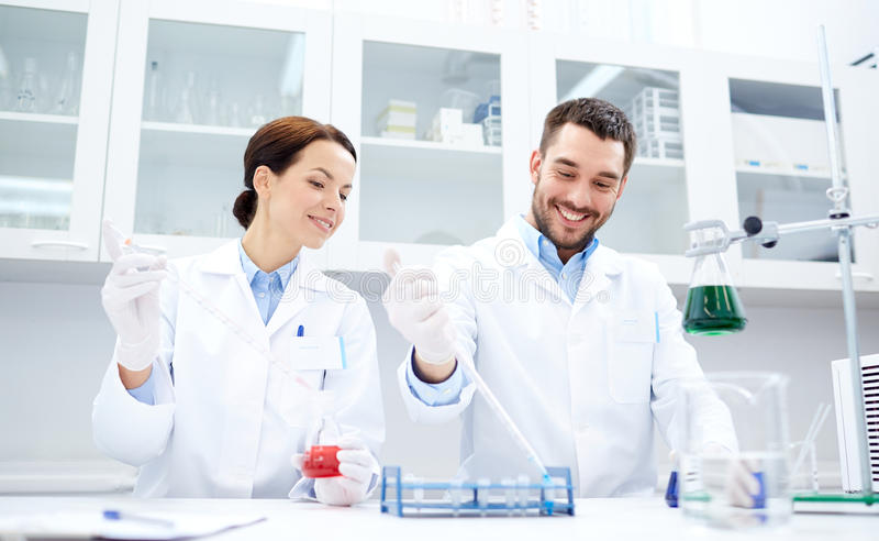 Young scientists making test or research in lab. Science, chemistry, technology, biology and people concept - young scientists with pipette and flask making test stock photo