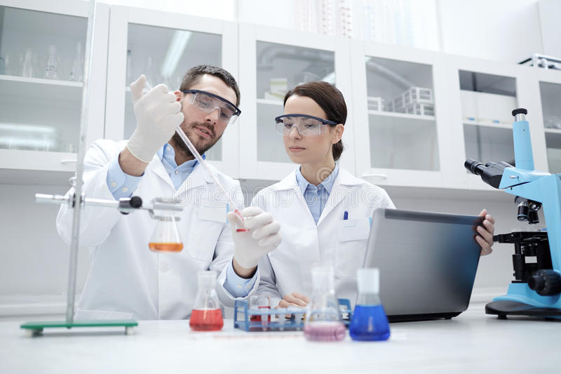 Young scientists making test or research in lab. Science, chemistry, technology, biology and people concept - young scientists with pipette and glass making test royalty free stock photo